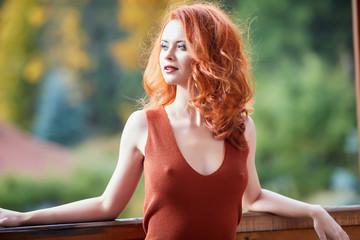 Beauty Romantic Girl Outdoors enjoying nature. Beautiful autumn red hair model with waving glow hair.Sun light on sunset. Portrait of romantic female Wall mural