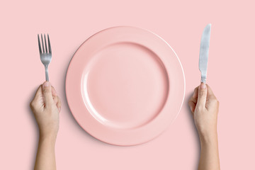 Pink plate with silver fork and knife on pink background with clipping path