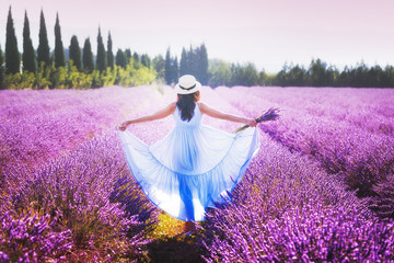 Provence, France. Beautiful young woman in a blue dress and straw hat walking between lavender in  Provence national park in France.