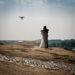 Two newlyweds kissing while a drone takes them. Belgrade on the background