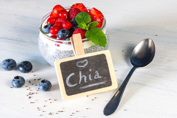 Chia seed pudding with fresh berries and a nostalgic spoon, decoratet on white wooden ground