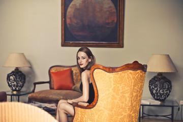 Woman sitting in an elegant room.