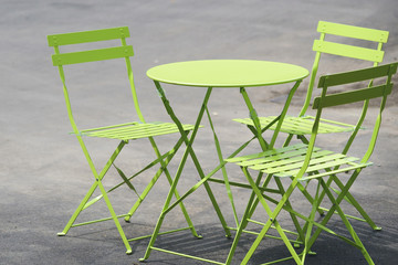 Green table and chairs stand on street in London