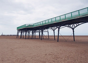 view of the historic victorian pier at saint annes on sea in in lancashire with the beach at low tide looking out to sea