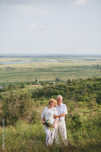 d76277dc568b Elderly couple in the white linen dress standing outdoors