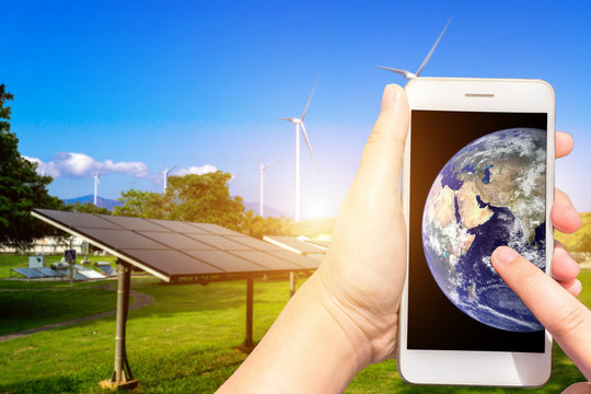 Use smartphone blurred images touch of World figure in solar panels with wind turbines against  landscape,Alternative energy concept,Clean energy,Elements of this earth image furnished by NASA.