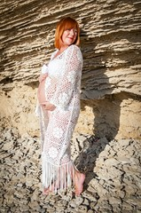 Young and beautiful red hair Caucasian woman in a white dress with a pregnancy belly posing with sandy rocks on the background.