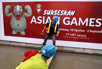 Workers are making pedestrian walkways in front of a banner of the18th Asian Games in Jakarta