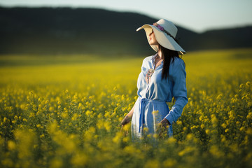Happy young woman is wearing fashion hat with bouquet of wildflowers in yellow field in sunset lights