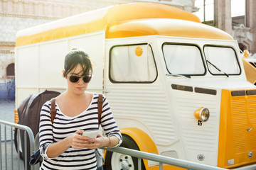 Young woman writing a message on her mobile, next to vintage style food truck