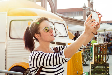 Young woman making a selfie, next to the food truck