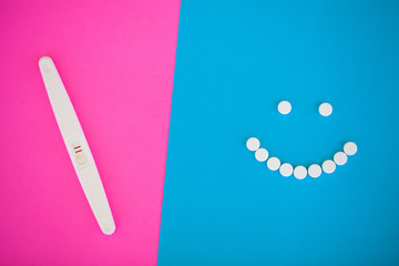 Pregnancy test. The result is positive with two strips and condom with contraceptive on colored background, Birth control pill, safe sex, healthcare concep