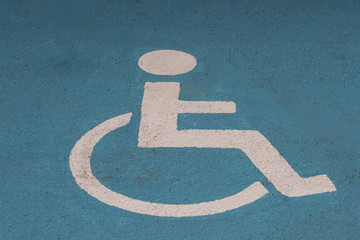 Handicapped or disabled parking sign painted on blue asphalt