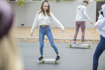 Happy teenage friends riding skateboard on the street