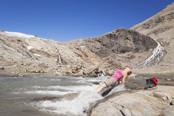 Austria, Carinthia, Grossglockner, Pasterze, woman enjoying refreshing break from hiking, High Tauern National Park