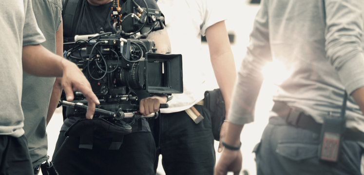 Blurred images of high definition video camera and lens on steady equipment support such as gimbal steady or stabilized shoulder rig and pan tilt shift head tripod for handheld filming moving object.