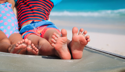 little boy and girl relax on beach, focus on feet