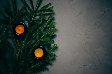 fir branch, and two candles on dark background, copy space
