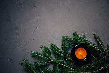 fir branch and candle on dark background, copy space
