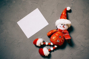 toy snowman and postcard on dark textured background, copy space