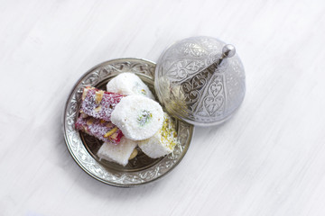 Traditional Turkish sweets lukum on a silver saucer with lid