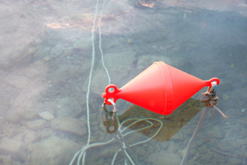 Red anchor buoy lies on a sea  water.
