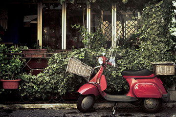 Fond de hotte en verre imprimé Scooter red vintage scooter in italy, retro motorcycle with foliage background
