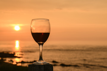 Red Wine. A wine glass half full of wine on a wooden post with the sun setting over the Pentland Firth, Caithness, Scotland