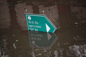 A road sign is seen submerged on a flooded road after heavy rains in New Delhi