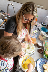 Mother with her 10 years old girl cooking in the kitchen, casual lifestyle photo series.
