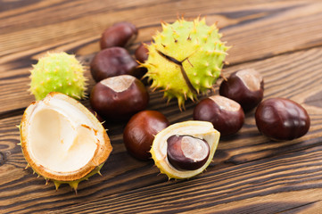 Heap of green prickly and brown smooth chestnuts on old wooden rustic brown table