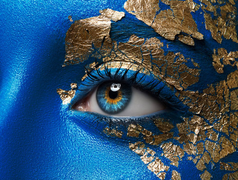 Artistic make-up and body art theme: portrait of a beautiful young girl model with blue make-up all over the body with gold foil for make-up