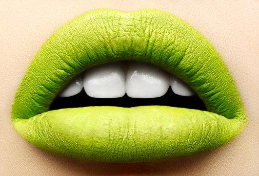 Macro and close-up creative make-up theme: beautiful female lips with a matte green lipstick