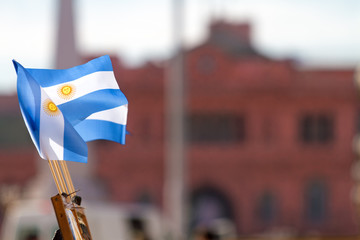 Argentine flags on a panel in a street stall selling souvenirs with Casa Rosada in the background