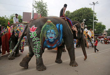 A mahout rides his elephant decorated with an image of Hindu god Shiva outside the Jagannath temple on the eve of the annual Rath Yatra, or chariot procession, in Ahmedabad