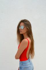c6657ff779 chica joven con gafas de sol de espejo sobre fondo blanco en lo que parece  una
