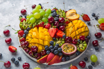 delicious fruits and berries platter.  Mango, kiwi, strawberry, grape, cherry, blueberry, peach and passion fruit