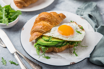 croissant sandwich with avocado, arugula and fried egg for breakfast