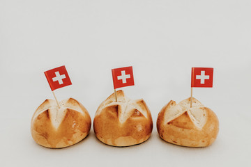 Swiss bread buns called in German 1. Augustweggen baked in Switzerland to celebrate Swiss National Day on August 1st. Swiss flag with white cross on red background.  White background, isolated.