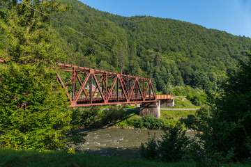 Red iron bridge across the swift river against the background of high green mountains