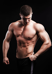 bodybuilder posing. Beautiful sporty guy male power. Fitness muscled man over black background.
