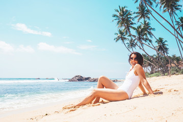 Happy smiling woman in white swimsuit lies on sand tropical beach. Island vacation