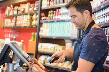 Shop clerk scanning bottle of alcohol