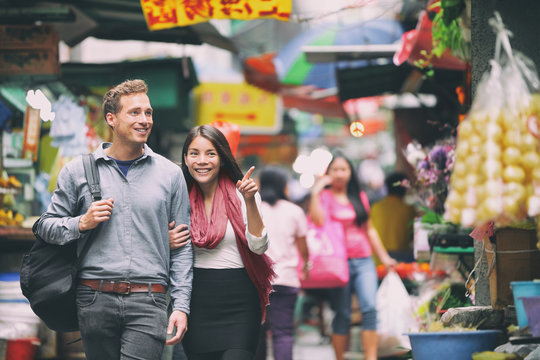 Interracial couple tourists walking shopping in chinese market in Hong Kong, China. Young people traveling in Asia looking at local street food. Asian woman, Caucasian man.