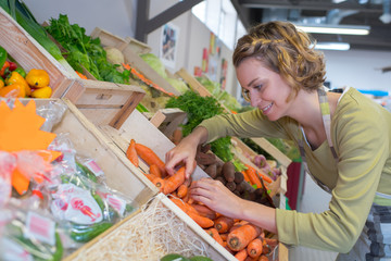 woman working in the vegetables section at a market