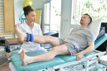 female physiotherapist massaging the leg of patient