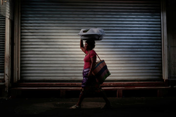 A merchant walks past a stall closed during a national strike at the Oriental Market in Managua