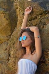 1c34c5961c mujer joven atractiva con gafas de sol en las rocas posando de forma  relajada junto a