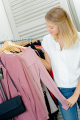 Lady looking at clothes on a rail, holding pink top