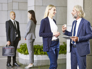 multinational corporate people standing talking in lobby of modern office building